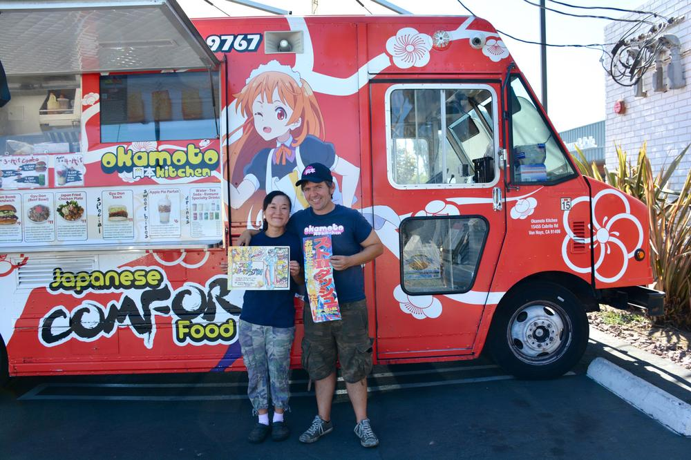 Chizuru and Gerald Abraham stand in front of Okamoto Kitchen holding the truck's menu