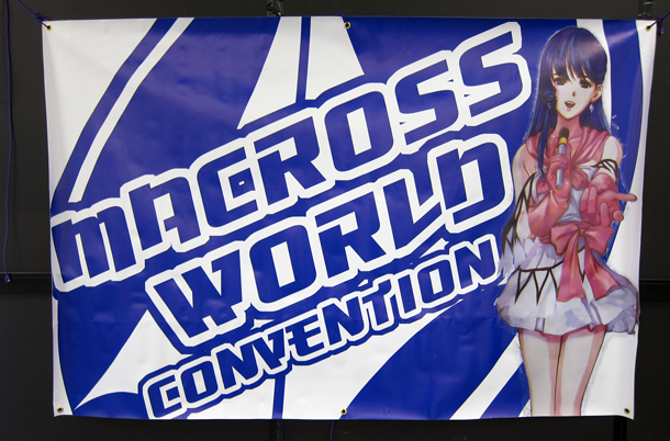 Macross World Convention Sign with an anime girl holding a mic and singing